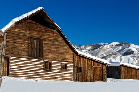 ski runs: Historic Steamboat Springs barn on snowy hill with ski area lifts and slopes in background