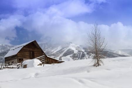 Historic Steamboat Springs barn on snowy hill with ski area lifts and slopes in background Stock Photo - 18113364
