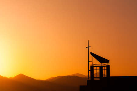 Silhouetted cross against dramatic sunset sky over mountains Stock Photo - 18167621
