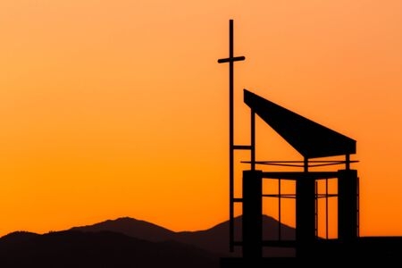Silhouetted crucifix against dramatic sunset sky over mountains Stock Photo - 18167616