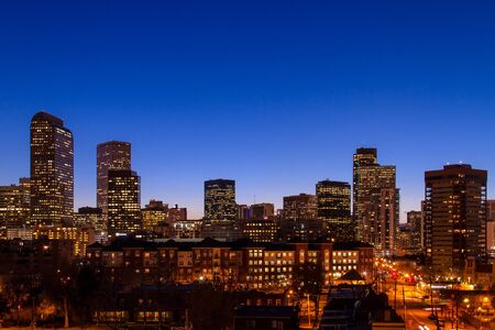 denver skyline: Denver Colorado skyline at dusk during the blue hour with lighted buildings and streets