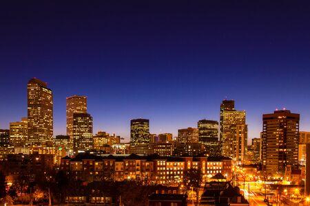 denver co: Primer plano de Denver Colorado horizonte al anochecer durante la hora azul con edificios iluminados y las calles
