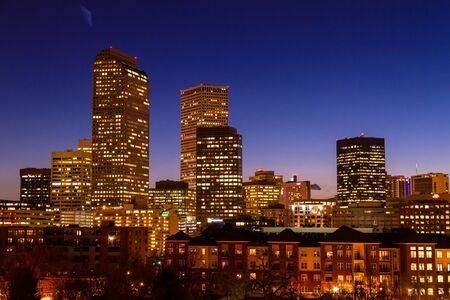 Close up of Denver Colorado skyline at dusk during the blue hour with lighted buildings and streets