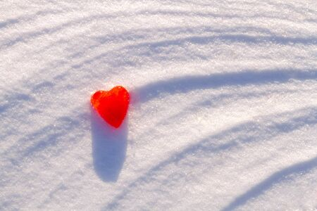 Red ice heart on freshly fallen snow with curved pattern on a sunny day Stock Photo - 18457682