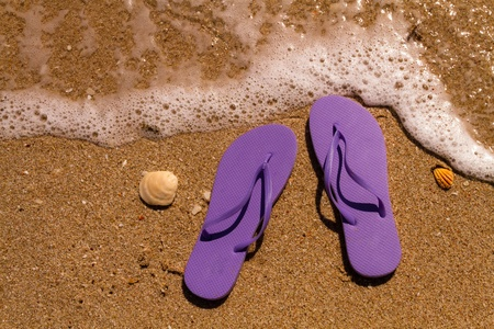 Purple flip flops on a sandy beach with ocean water washing up on shore and sea shells Stock Photo - 18837924