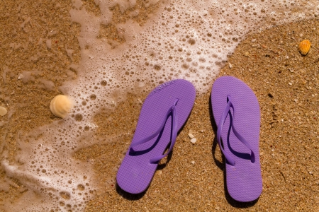 Purple flip flops laying on the sand with ocean water washing up on shore and sea shells Stock Photo - 18837922