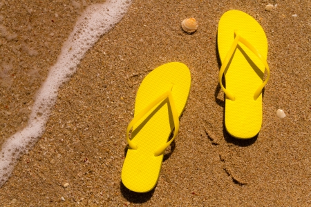 Bright yellow flip flops on a sandy beach with ocean water washing up on shore and sea shells Stock Photo - 18837927