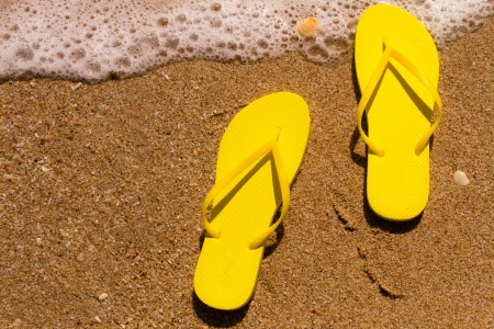 Pair of bright yellow flip flops laying on the sand with ocean wave washing up on the beach Stock Photo - 18837921