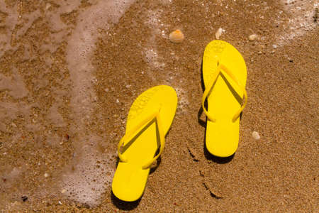 Bright yellow flip flops laying on the sand with ocean water washing up on shore and sea shells Stock Photo - 18837919