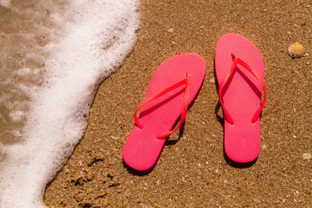 Pair of bright orange flip flops laying on the sand with ocean wave washing up on the beach Stock Photo - 18837918