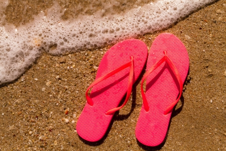 Bright orange flip flops laying on the sand with ocean water washing up on shore and sea shells Stock Photo - 18837925