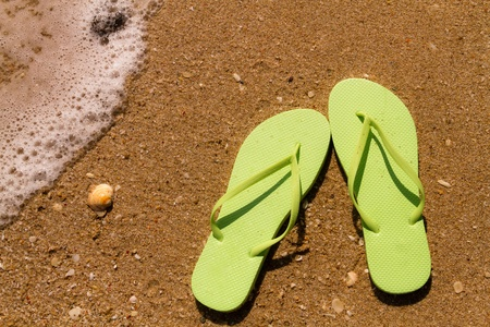 Bright green flip flops on a sandy beach with ocean water washing up on shore and sea shells Stock Photo - 18837923