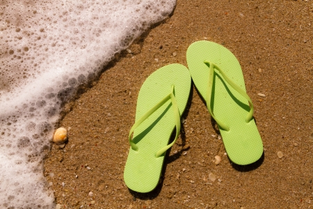 Pair of bright green flip flops laying on the sand with ocean wave washing up on the beach Stock Photo - 18837933
