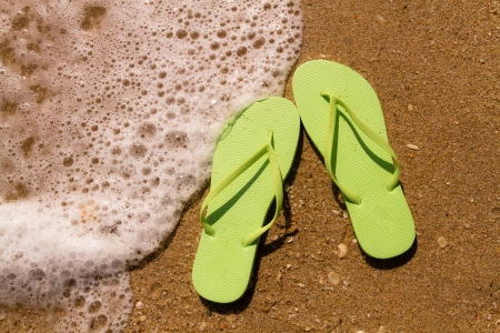 Bright green flip flops laying on the sand with ocean water washing up on shore and sea shells Stock Photo - 18837920