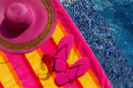 Pair of bright pink flip flops by the pool on a bright orange, pink, red and yellow striped towel with sunglasses and big pink floppy hat Stock Photo - 18837939