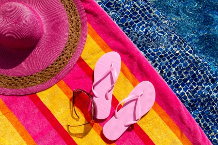 Pair of light pink flip flops by the pool on a bright orange, pink, red and yellow striped towel with sunglasses and big pink floppy hat Stock Photo - 18837935