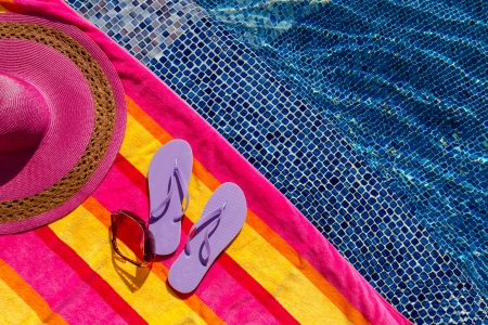 Pair of light purple flip flops by the pool on a bright orange, pink, red and yellow striped towel with sunglasses and big pink floppy hat Stock Photo - 18837937