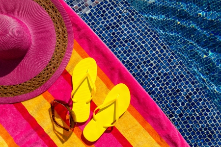 Pair of bright yellow flip flops by the pool on a bright orange, pink, red and yellow striped towel with sunglasses and big pink floppy hat Stock Photo - 18837938