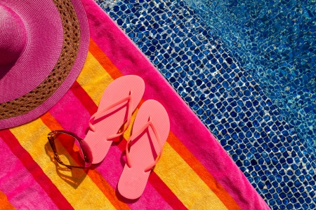 Pair of orange flip flops by the pool on a bright orange, pink, red and yellow striped towel with sunglasses and big pink floppy hat Stock Photo - 18837934