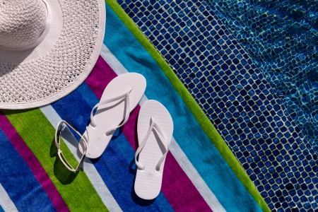 Pair of white flip flops by the pool on a bright blue, green, purple and white striped towel with sunglasses and big white floppy hat Stock Photo - 18837932