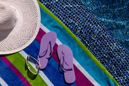 Pair of light purple flip flops by the pool on a bright blue, green, purple and white striped towel with sunglasses and big white floppy hat Stock Photo - 18837928
