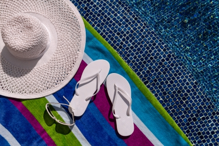 Pair of white flip flops by the pool on a bright blue, green, purple and white striped towel with sunglasses and big white floppy hat Stock Photo - 18837931