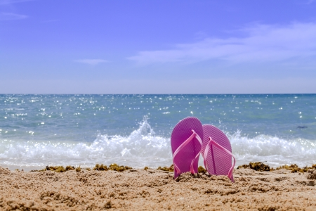 Light pink pair flip flops sticking up on a sandy beach with water and waves crashing on the beach