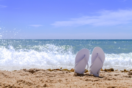 White pair flip flops sticking up on a sandy beach with water and waves crashing on the beach Stock Photo - 18964257