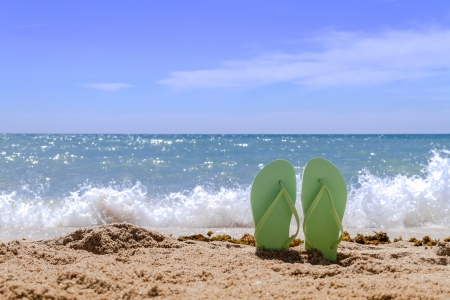 Green pair flip flops sticking up on a sandy beach with water and waves crashing on the beach