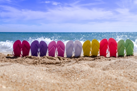 water shoes: Line of brightly colored flip flops arranged in a rainbow on beach with waves breaking on beach Stock Photo