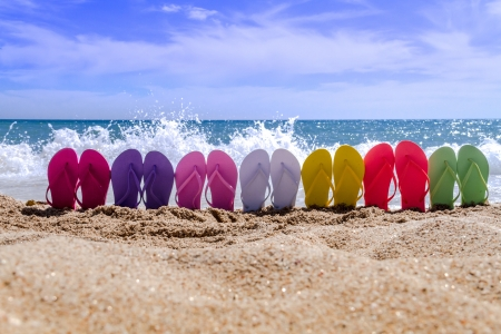 Line of brightly colored flip flops arranged in a rainbow on beach with large waves breaking on sandy shore