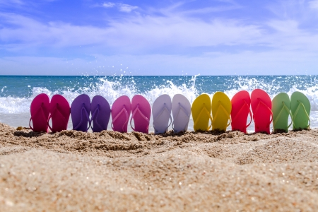 Line of brightly colored flip flops arranged in a rainbow on beach with waves breaking on sandy shore Stock Photo