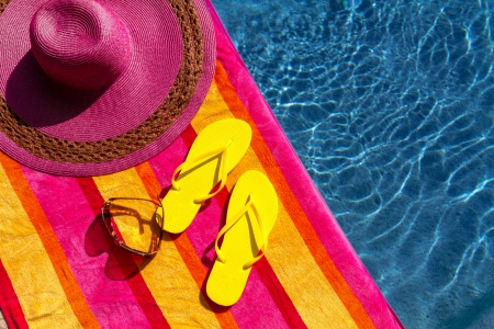 Pair of bright yellow flip flops by the pool on a bright orange, pink, red and yellow striped towel with sunglasses and big pink floppy hat Stock Photo - 19159367
