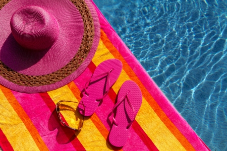 Pair of bright pink flip flops by the pool on a bright orange, pink, red and yellow striped towel with sunglasses and big pink floppy hat Stock Photo - 19159370
