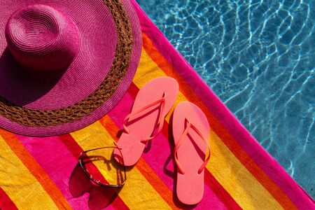 Pair of orange flip flops by the pool on a bright orange, pink, red and yellow striped towel with sunglasses and big pink floppy hat Stock Photo - 19159368