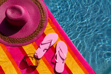 Pair of light pink flip flops by the pool on a bright orange, pink, red and yellow striped towel with sunglasses and big pink floppy hat Stock Photo - 19159364