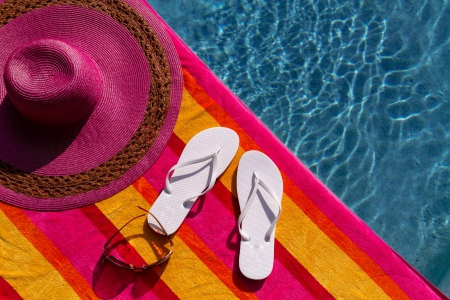 Pair of white flip flops by the pool on a bright orange, pink, red and yellow striped towel with sunglasses and big pink floppy hat Stock Photo - 19159359