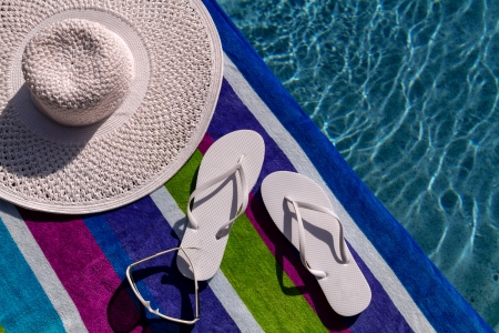 Pair of white flip flops by the pool on a bright blue, green, purple and white striped towel with sunglasses and big white floppy hat Stock Photo