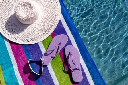 Pair of light purple flip flops by the pool on a bright blue, green, purple and white striped towel with sunglasses and big white floppy hat Stock Photo - 19159357