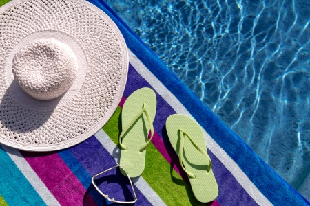 Pair of green flip flops by the pool on a bright blue, green, purple and white striped towel with sunglasses and big white floppy hat