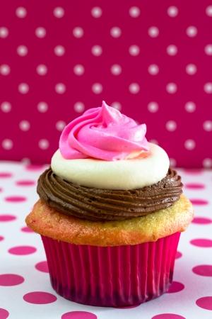 napoletana: Singolo napoletano smerigliato cupcake su tovaglia rosa polka, e lo sfondo