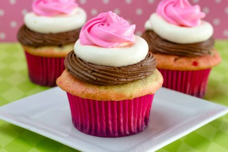 3 neapolitan frosted cupcakes on white plate with green diamond tablecloth, and pink polka background