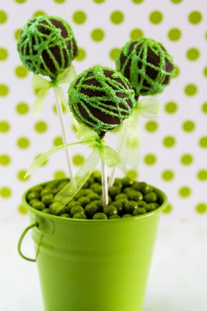 Chocolate cake pops with green swirl glitter sugar decorations against white background with green polka dots, portrait orientation photo