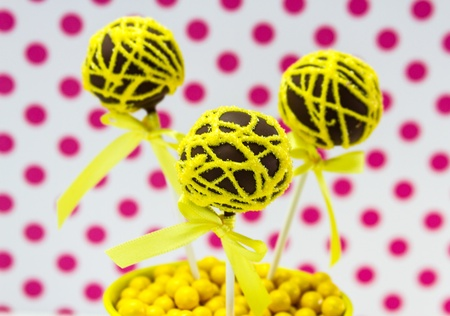 Chocolate cake pops with yellow swirl glitter sugar decorations against white background with pink polka dots photo