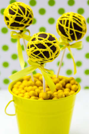 Chocolate cake pops with yellow swirl glitter sugar decorations against white background with green polka dots, portrait orientation photo