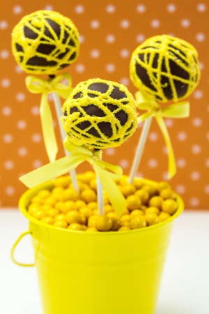 Chocolate cake pops with yellow swirl glitter sugar decorations against orange polka dot background, portrait orientation photo