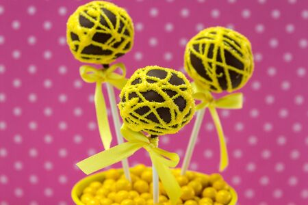 Chocolate cake pops with yellow swirl glitter sugar decorations against pink polka dot background photo