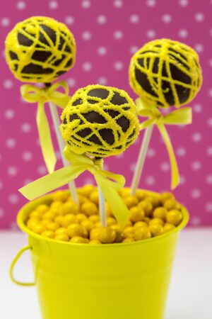 Chocolate cake pops with yellow swirl glitter sugar decorations against pink polka dot background, portrait orientation photo