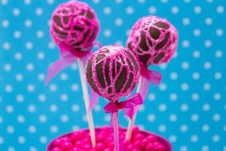 Chocolate cake pops with pink swirl glitter sugar decorations against blue polka dot background photo