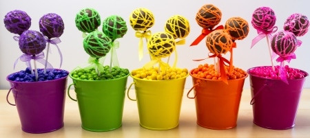 Line of rainbow colored chocolate cake pops in colored buckets and colored candy balls